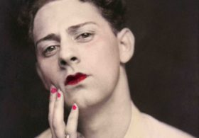 Man in makeup wearing ring. Photograph from a photo booth, with highlights of color. United States, circa 1920. © Sebastian Lifshitz Collection