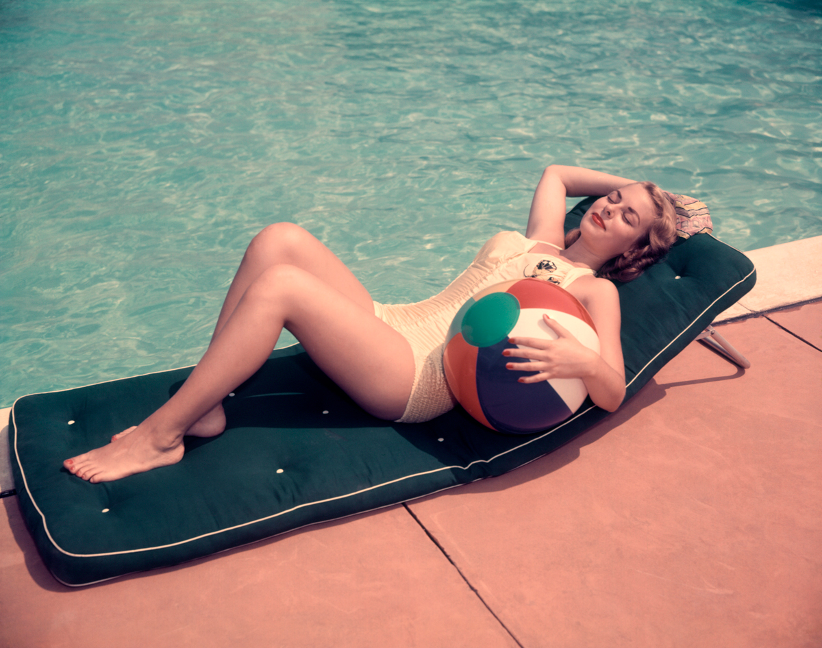 1950s: Woman Sun Bathing On Green Mat By Edge Side Of Pool Water Recline Holding Beach Ball By Her Side Relax. © H. Armstrong Roberts / Getty Images