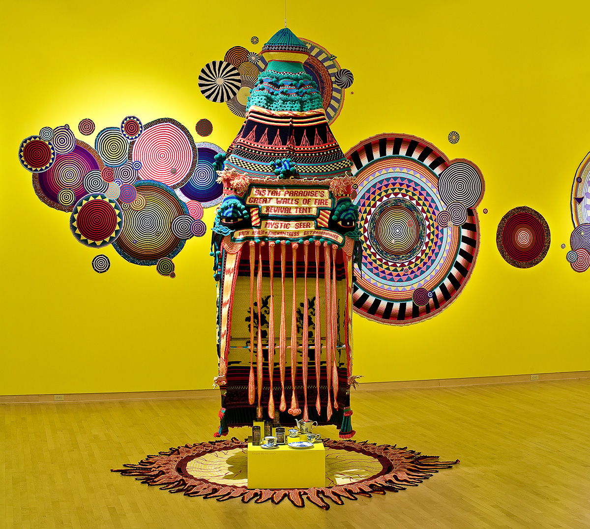 Xenobia Bailey, Sistah Paradise's Great Wall of Fire Tent (installation view, John Michael Kohler Arts Center), 1993; acrylic and cotton yarn and mixed media. Courtesy of the artist.