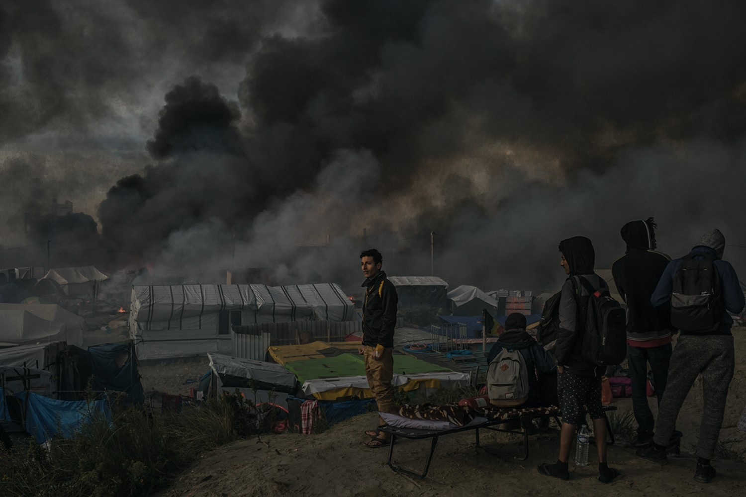 "MAURICIO LIMARefugees watch a huge plume of smoke as dozens of res burn huts and makeshift shops at the camp called the ""Jungle"", in Calais, northern France October 26, 2016. © Mauricio Lima for The New York Times"