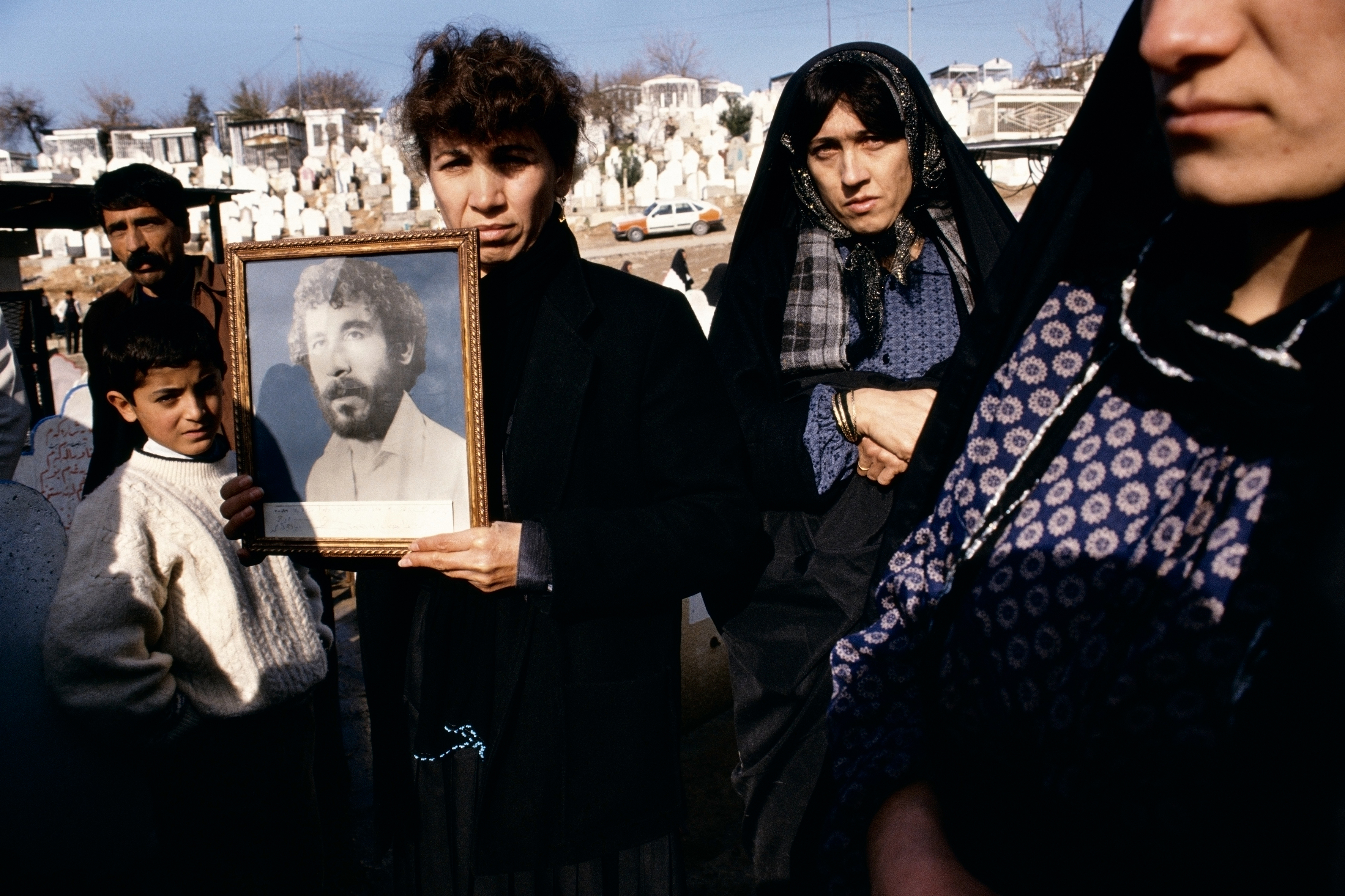 Susan Meiselas Photographs of 20-year-old Kamaran Abdullah Saber are held by his family at Saiwan Hill cemetery. He was killed in July 1991 during a student demonstration against Saddam Hussein, Kurdistan, Northern Iraq, 1991. © Susan Meiselas