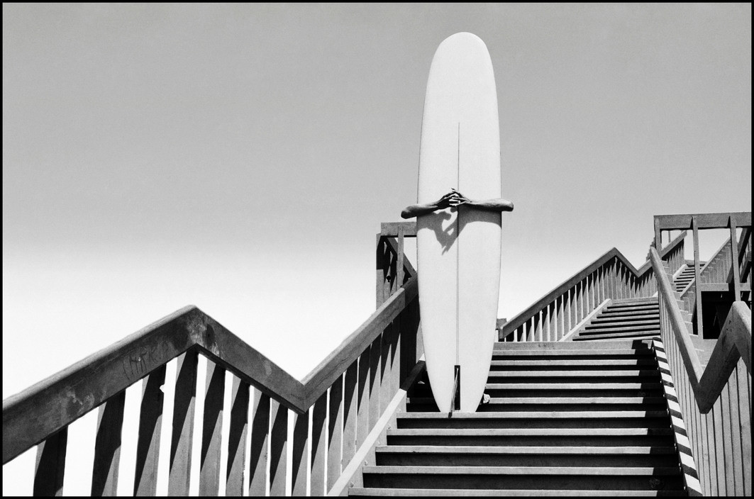 Dennis Stock, Man holding a surfboard on beach steps in Corona Del Mar, California 1968, from California Trip