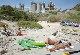 Throughout the series, which has just been published as a book by Mack, sun-seekers set up camp in car parks; swimming pools appear as mini oases in a desert of grey concrete; and cranes and cooling towers loom awkwardly over beaches. The contrast between these built up, man-made environments and the sunbathers, who appear minute in scale, is amusingly surreal, but highlights our subservience towards industry, housing developments and superstores.