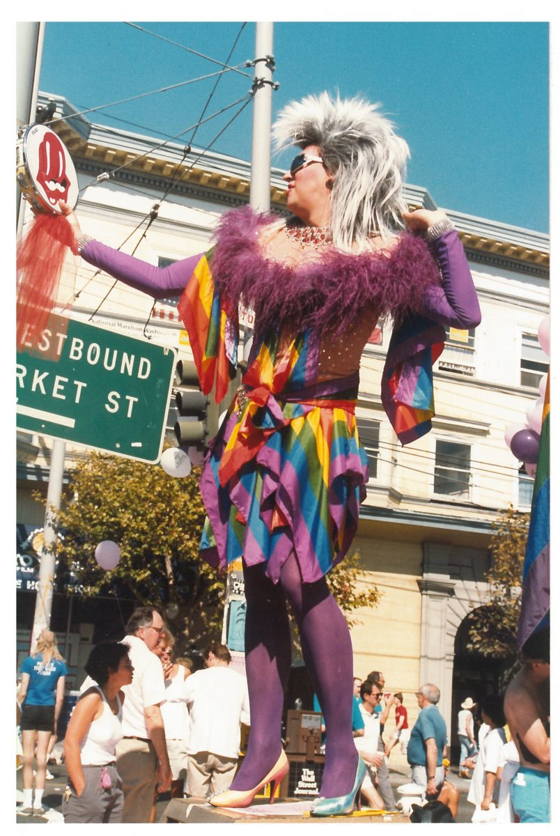 Gilbert Baker posing in a rainbow dress with a Rolling Stones tambourine during the 1987 Castro Street Fair; photograph by Robert Pruzan, collection of the GLBT Historical Society
